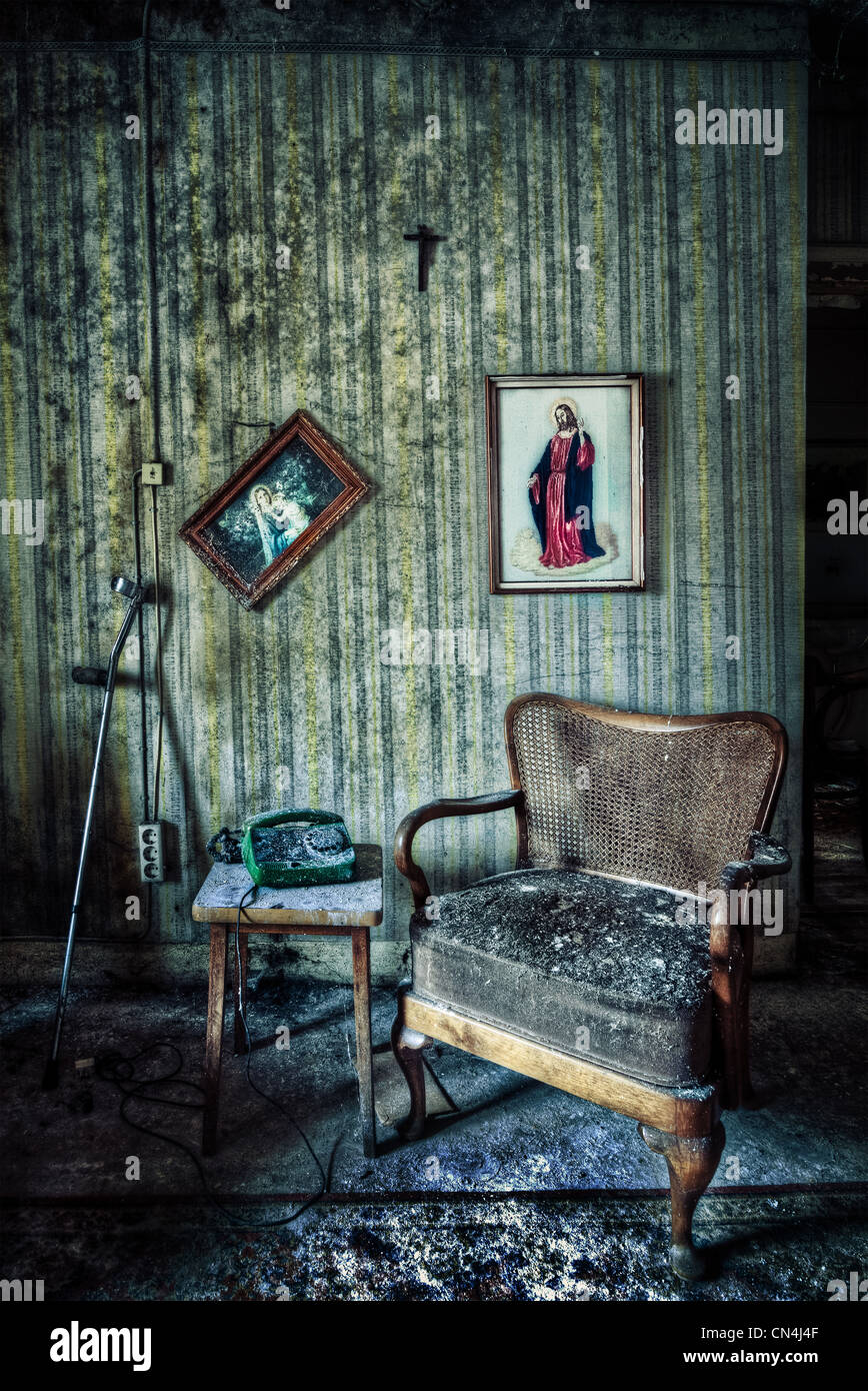 Abandoned room with chair and pictures - Stock Image