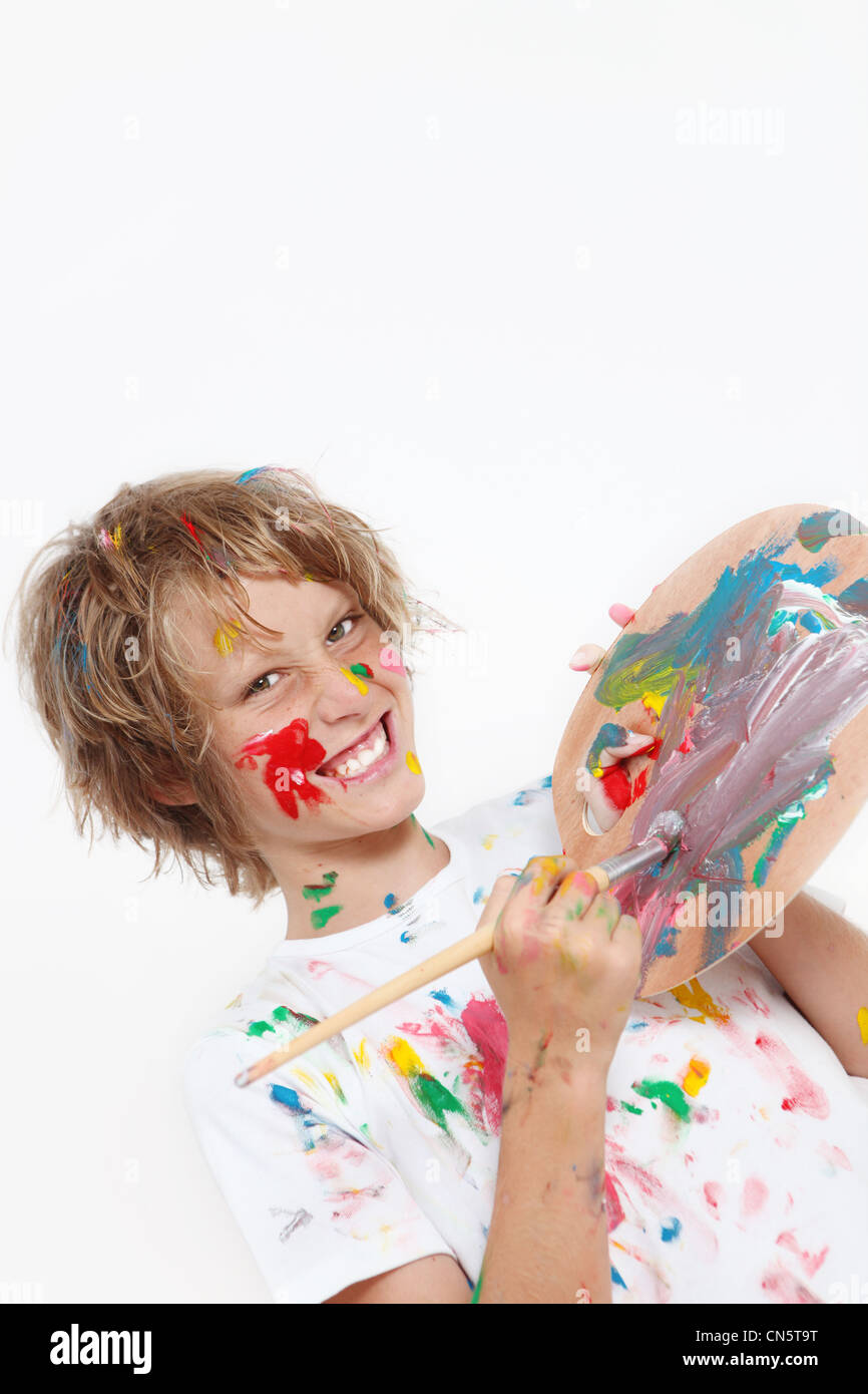 cheeky kid playing with paint - Stock Image