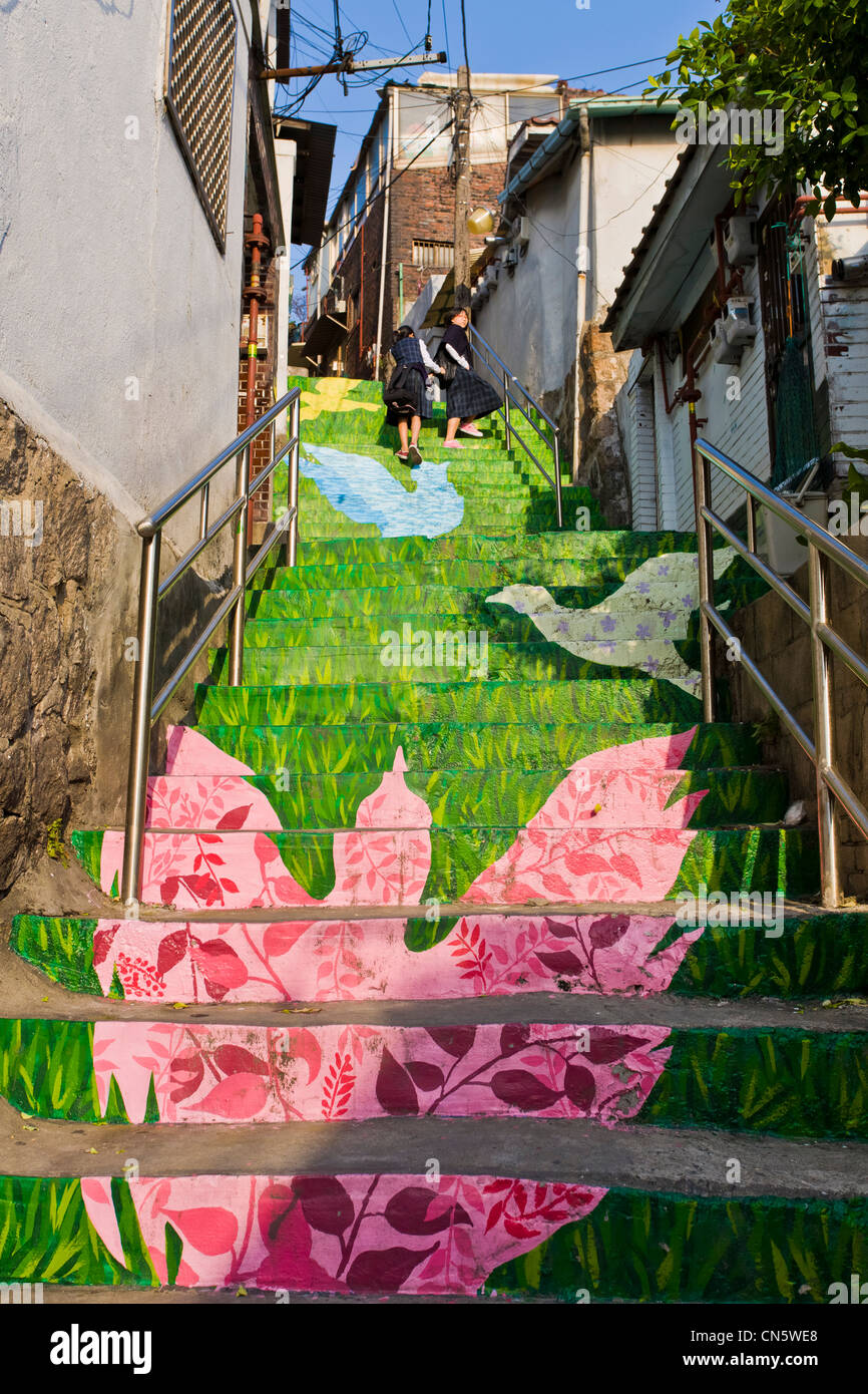 South Korea, Seoul, Daehangno District, two schoolgirls play on decorated public stairs. These works of art have - Stock Image