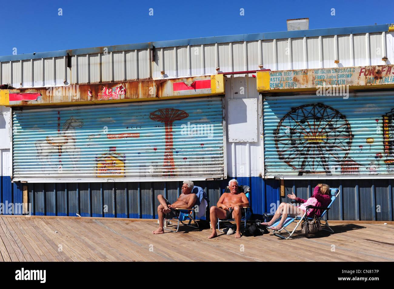 USA  New York City Brooklyn NY NYC Coney Island amusement park - three 3 older people sunbathe on the boardwalk Stock Photo