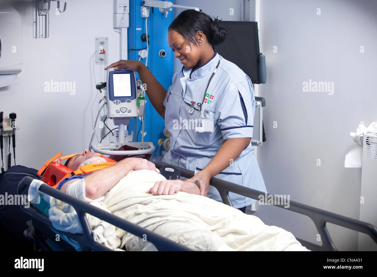 A young female accident and emergency nurse attends and patient UK Stock Photo