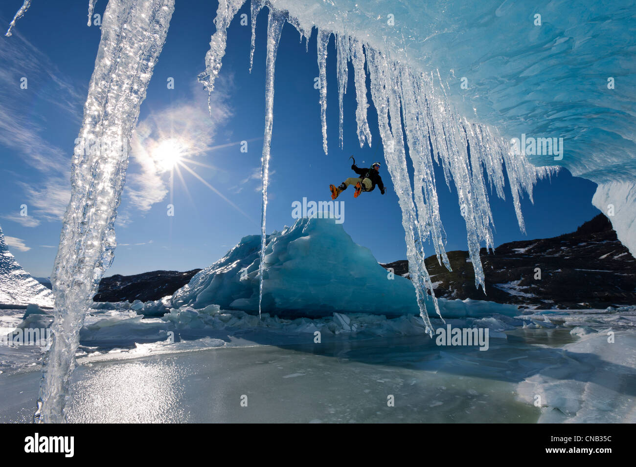 COMPOSITE: Sun shines through icicles hanging on an iceberg as an ice climber rappels over the edge, Mendenhall - Stock Image