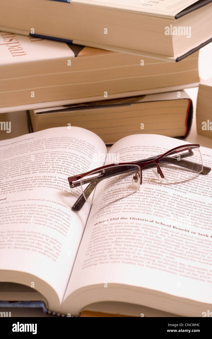 Pile of books with open book and reading glasses. - Stock Image