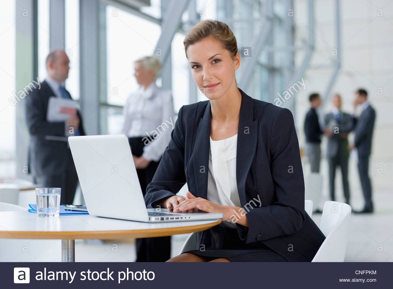 Portrait of confident businesswoman in suit sitting at laptop in lobby - Stock Image