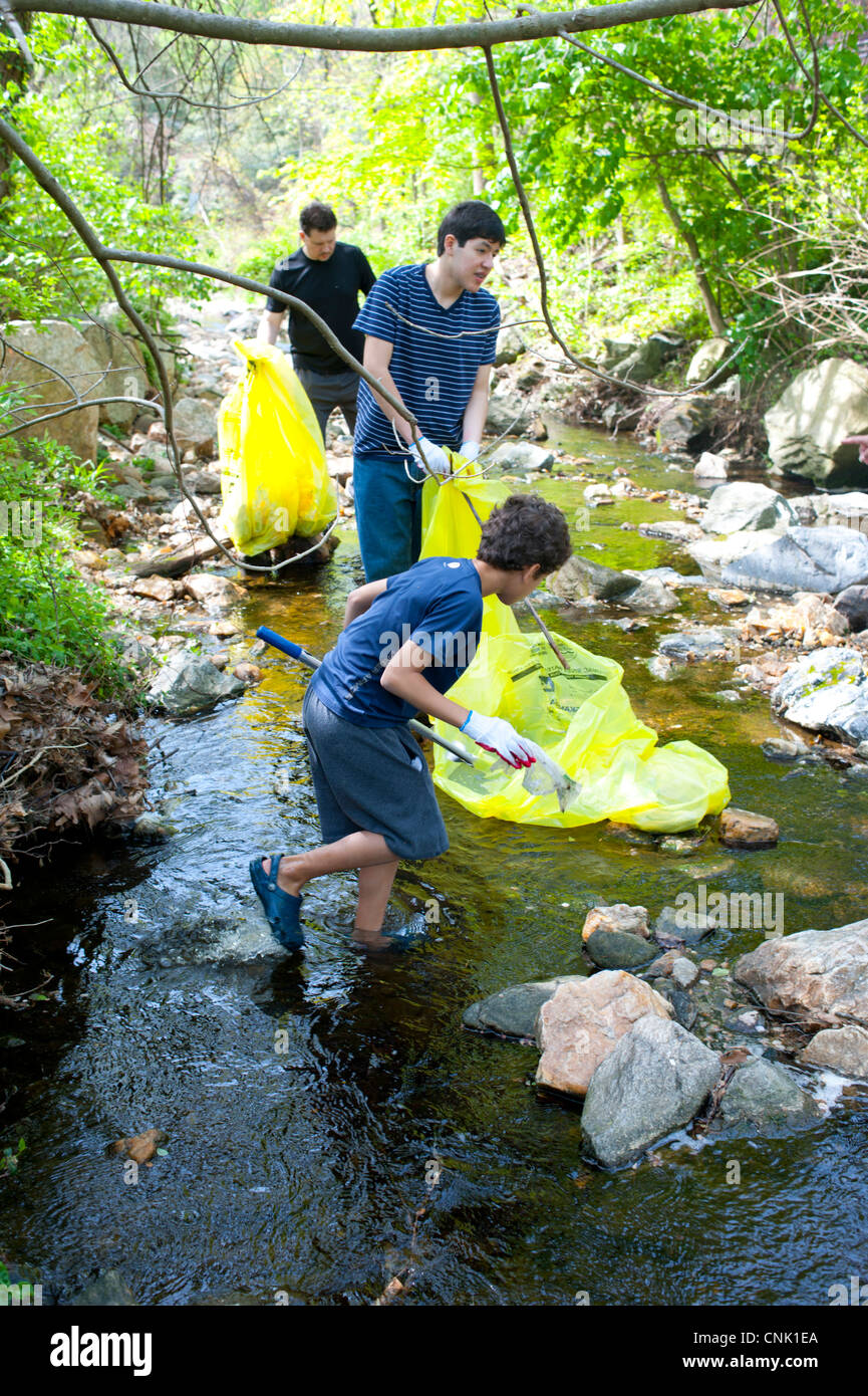 Earth Day Hispanic family cleans up garbage trash rubbish from a creek in Maryland USA Stock Photo
