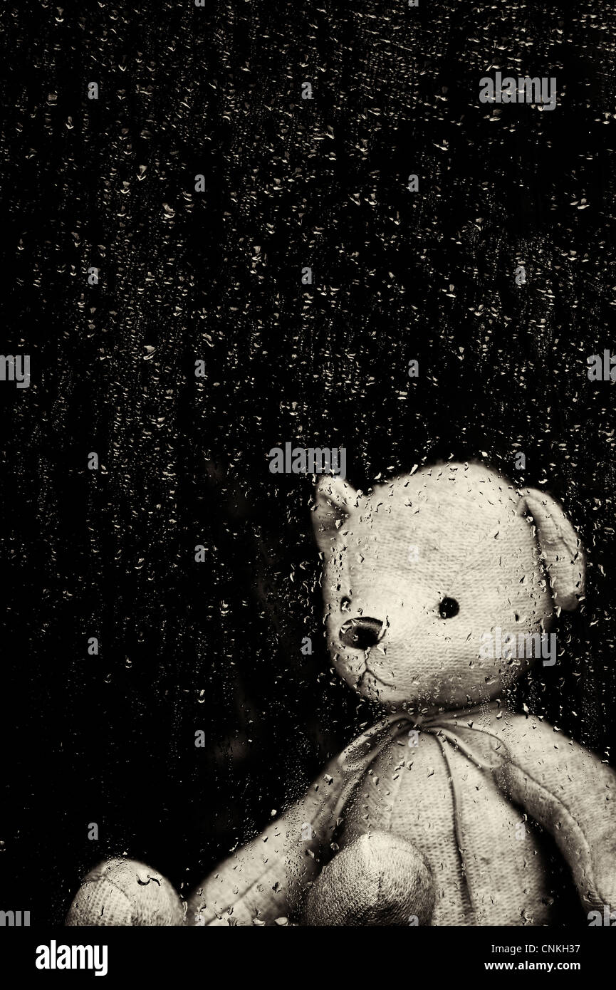 Sad Teddy bear looking through a window covered in rain drops. Sepia Toned - Stock Image