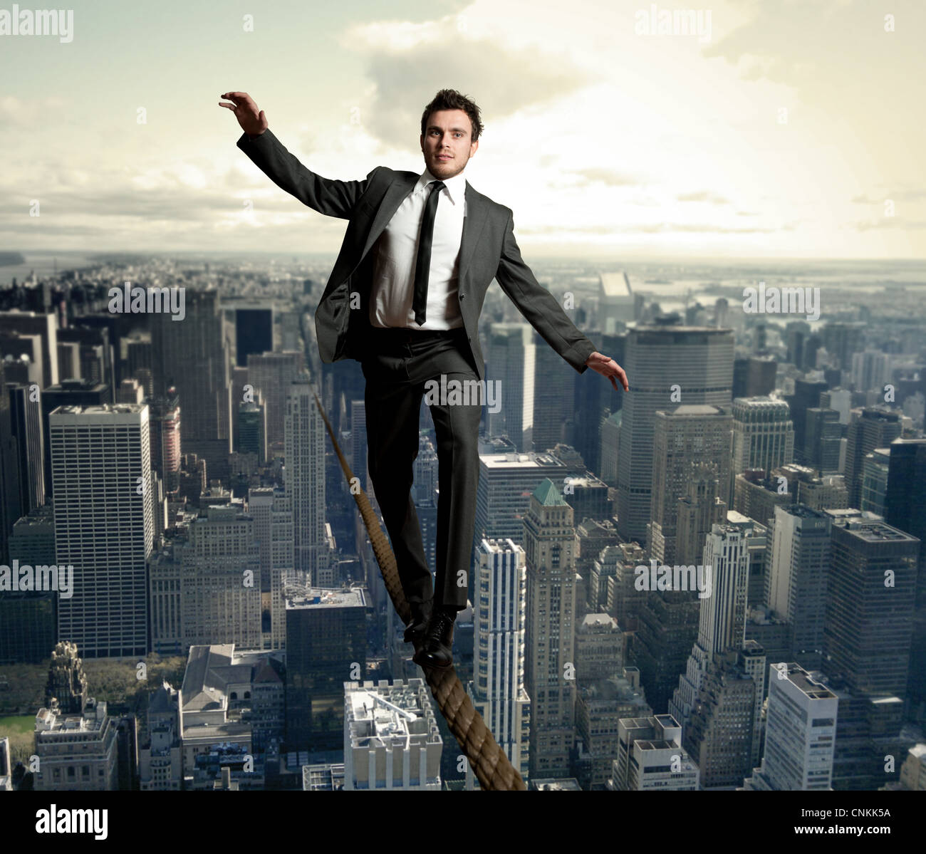 Businessman is balancing on a rope - Stock Image