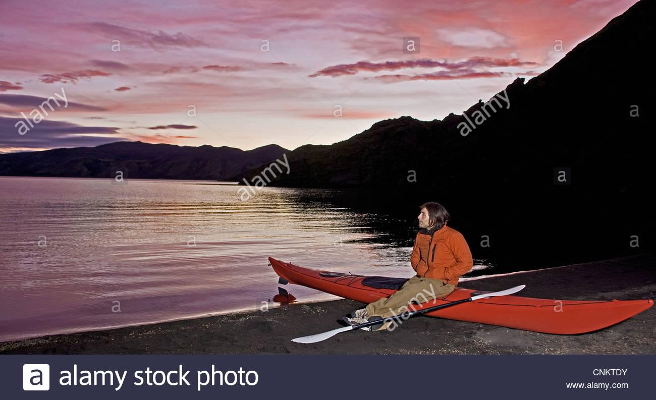 Woman sitting on kayak by still lake - Stock Image