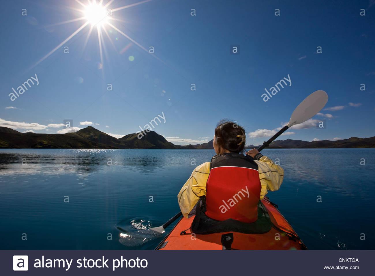 Woman rowing kayak in still lake - Stock Image