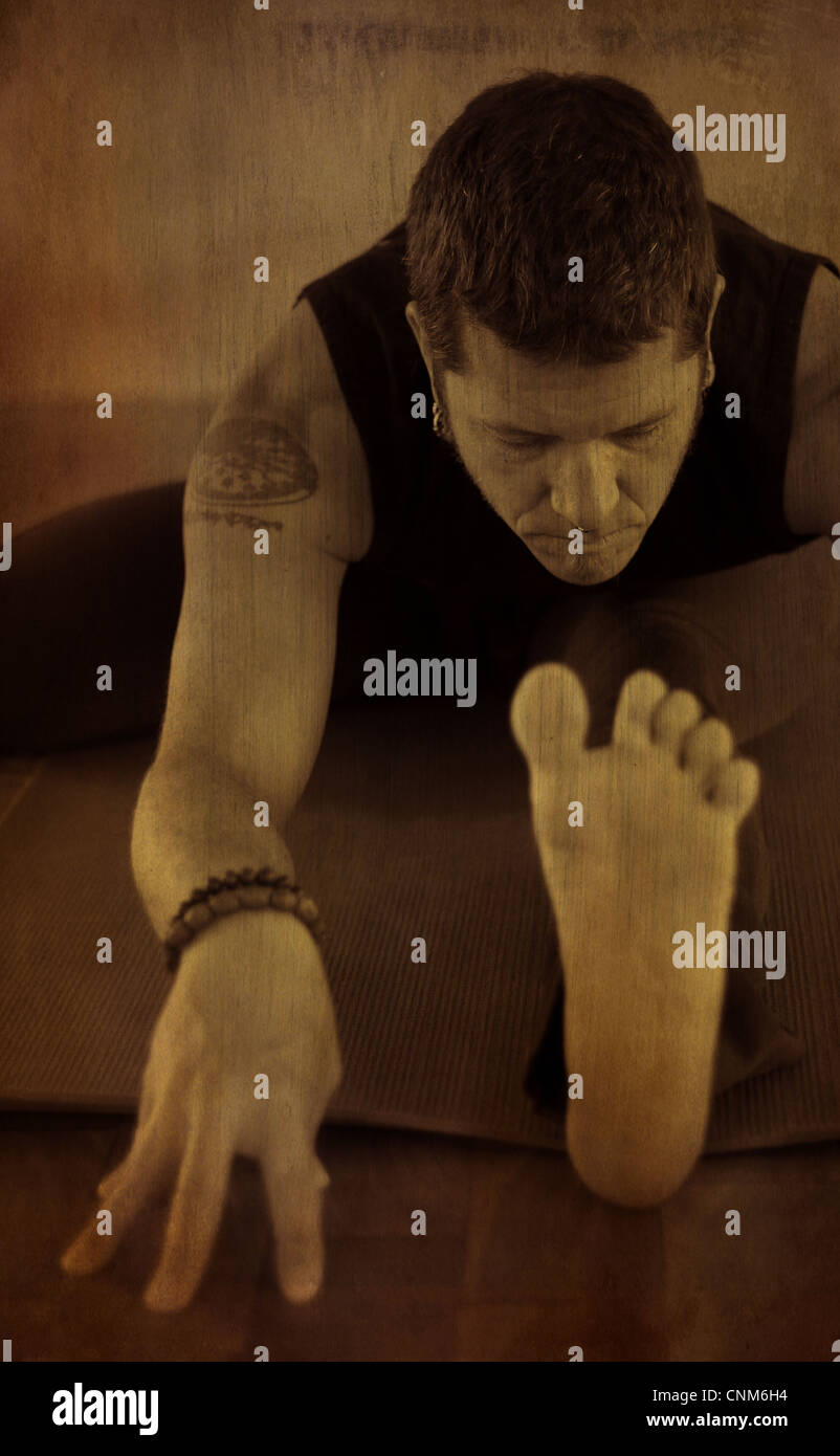 A man practicing yoga going into a sitting forward bend; a version of janusirsasana,. Photo treated with texture - Stock Image