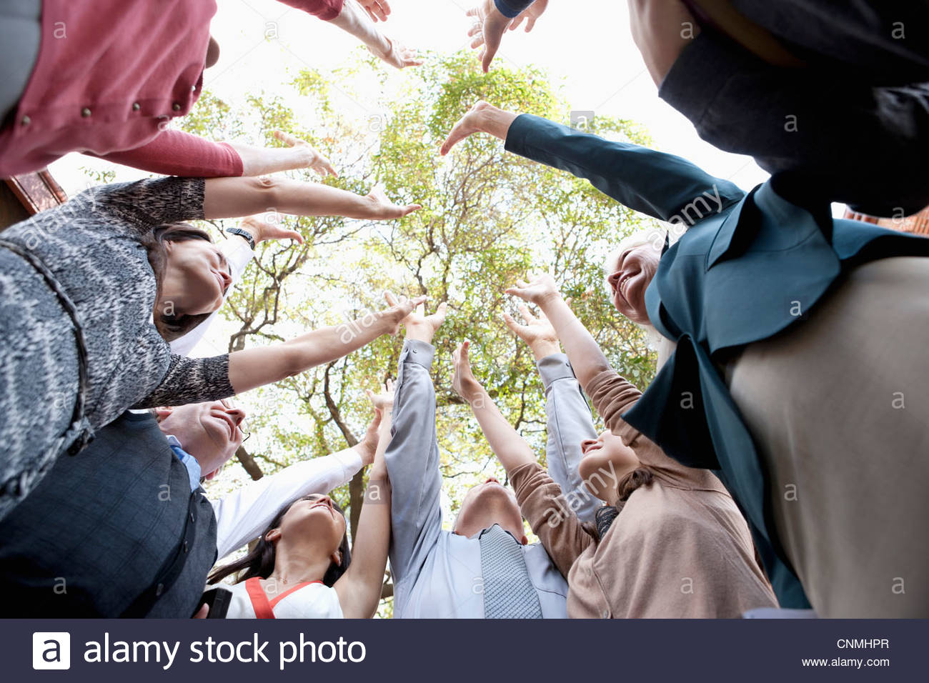 People in circle cheering together - Stock Image