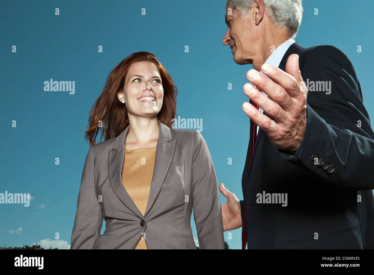 Business people talking against blue sky - Stock Image