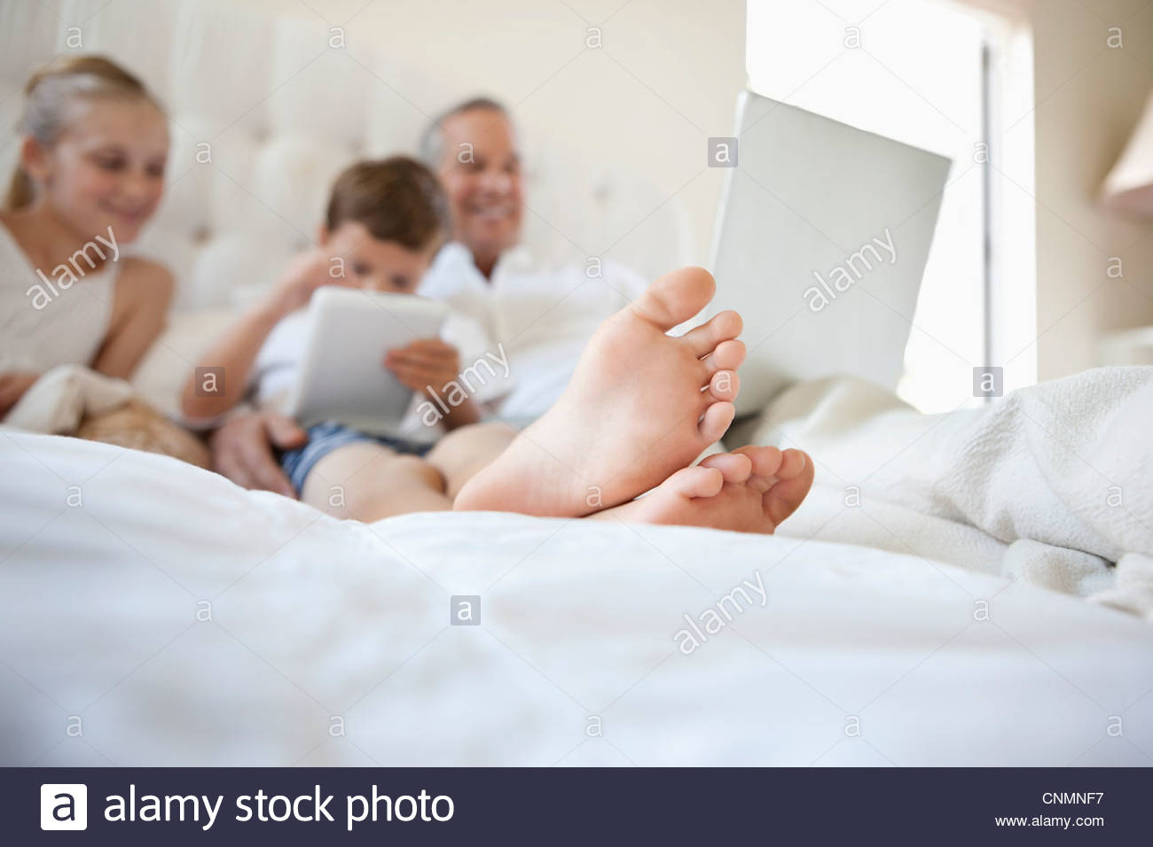 Close Up Of Boys Feet On Bed