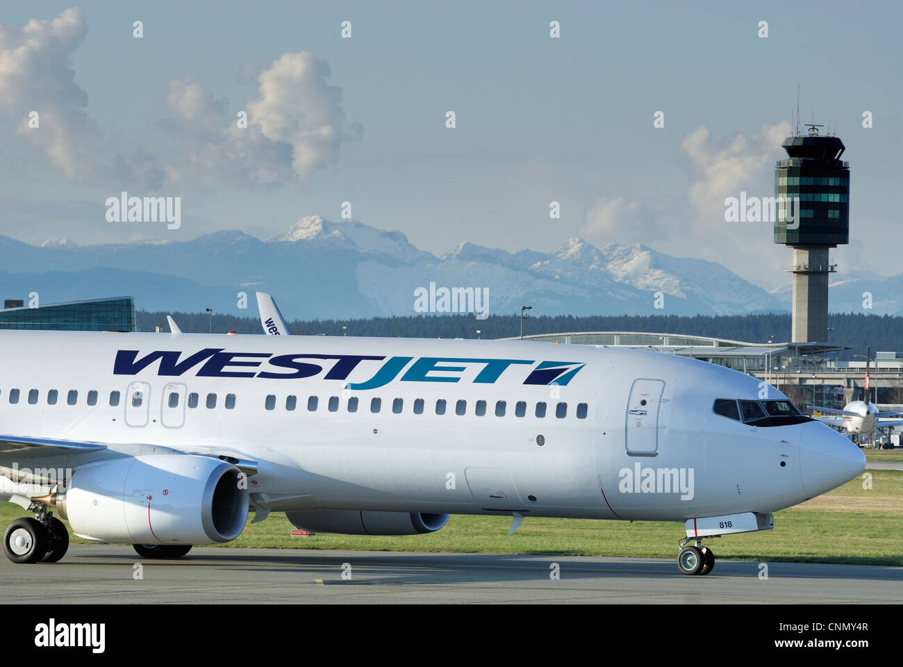 Close-up of a Westjet C-GWRG Boeing 737 (800) airliner taxiing down the runway at the Vancouver International airport. - Stock Image