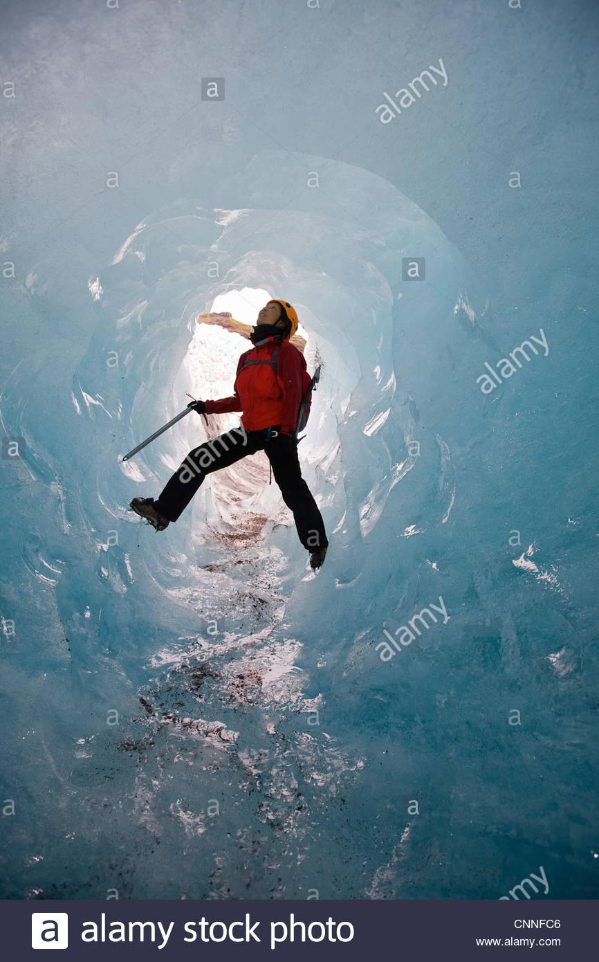 Climber scaling glacial cave - Stock Image