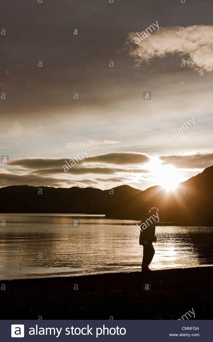 Man walking by still lake - Stock Image