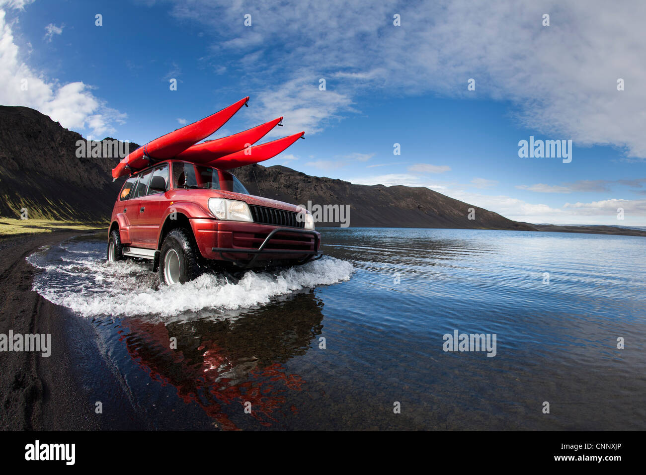 Jeep driving in shallow lake - Stock Image