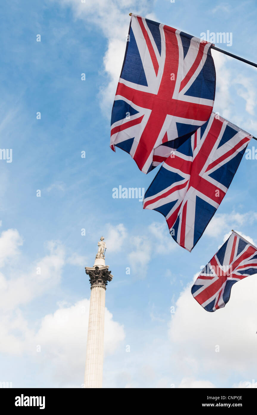British Union flags in row, with Nelson column in background. - Stock Image