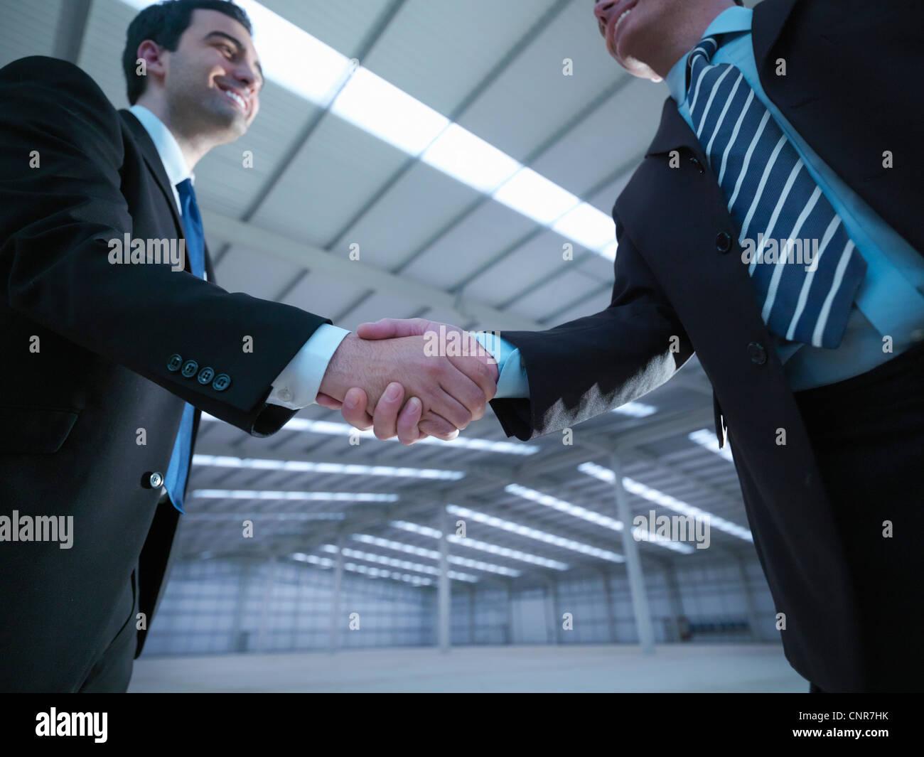 Businessmen shaking hands in warehouse - Stock Image