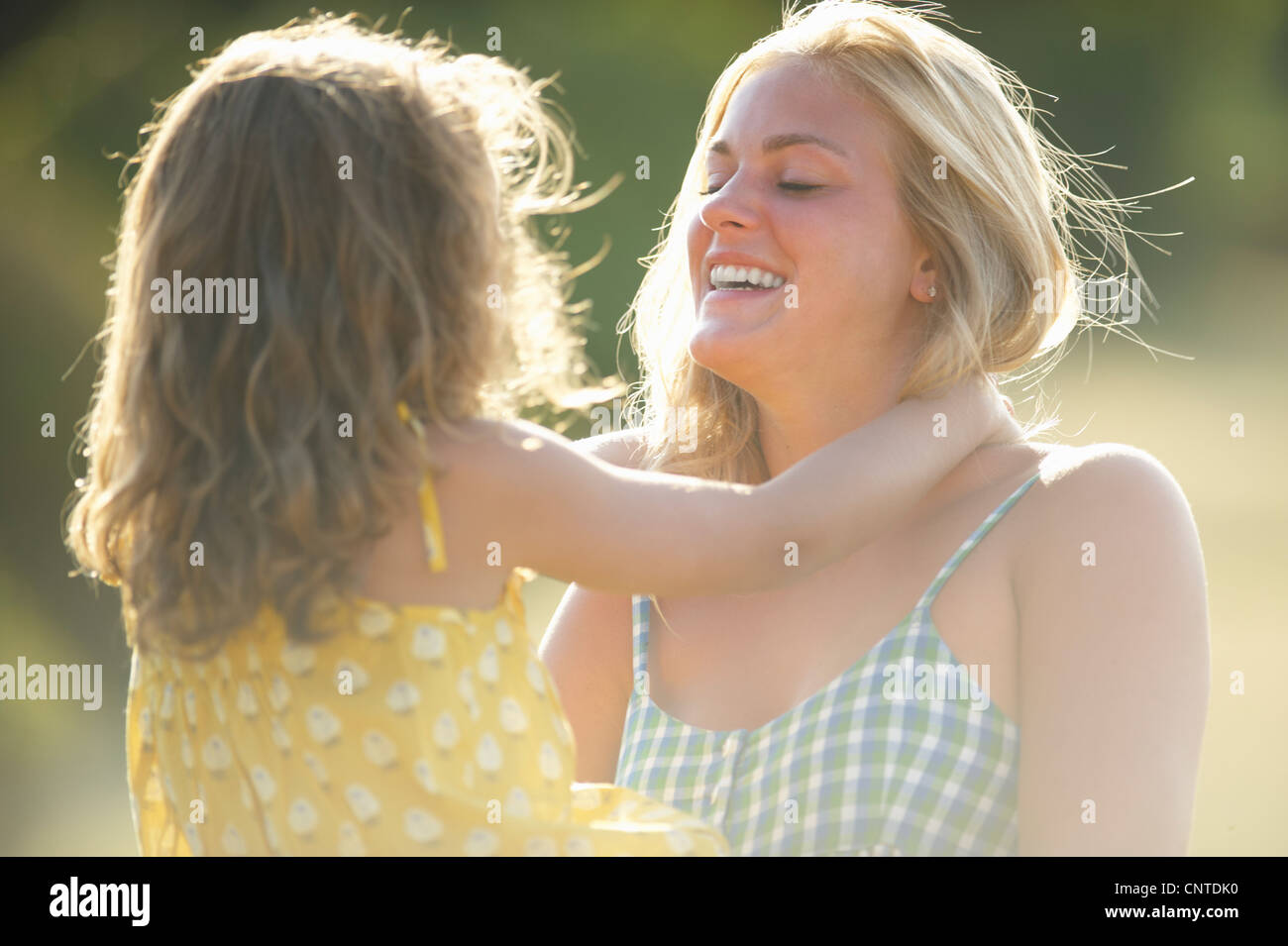 Mother holding daughter outdoors - Stock Image