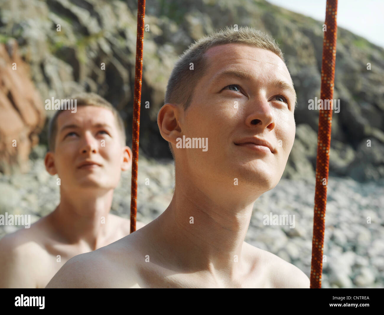 Rock climbers holding cord taut on beach - Stock Image