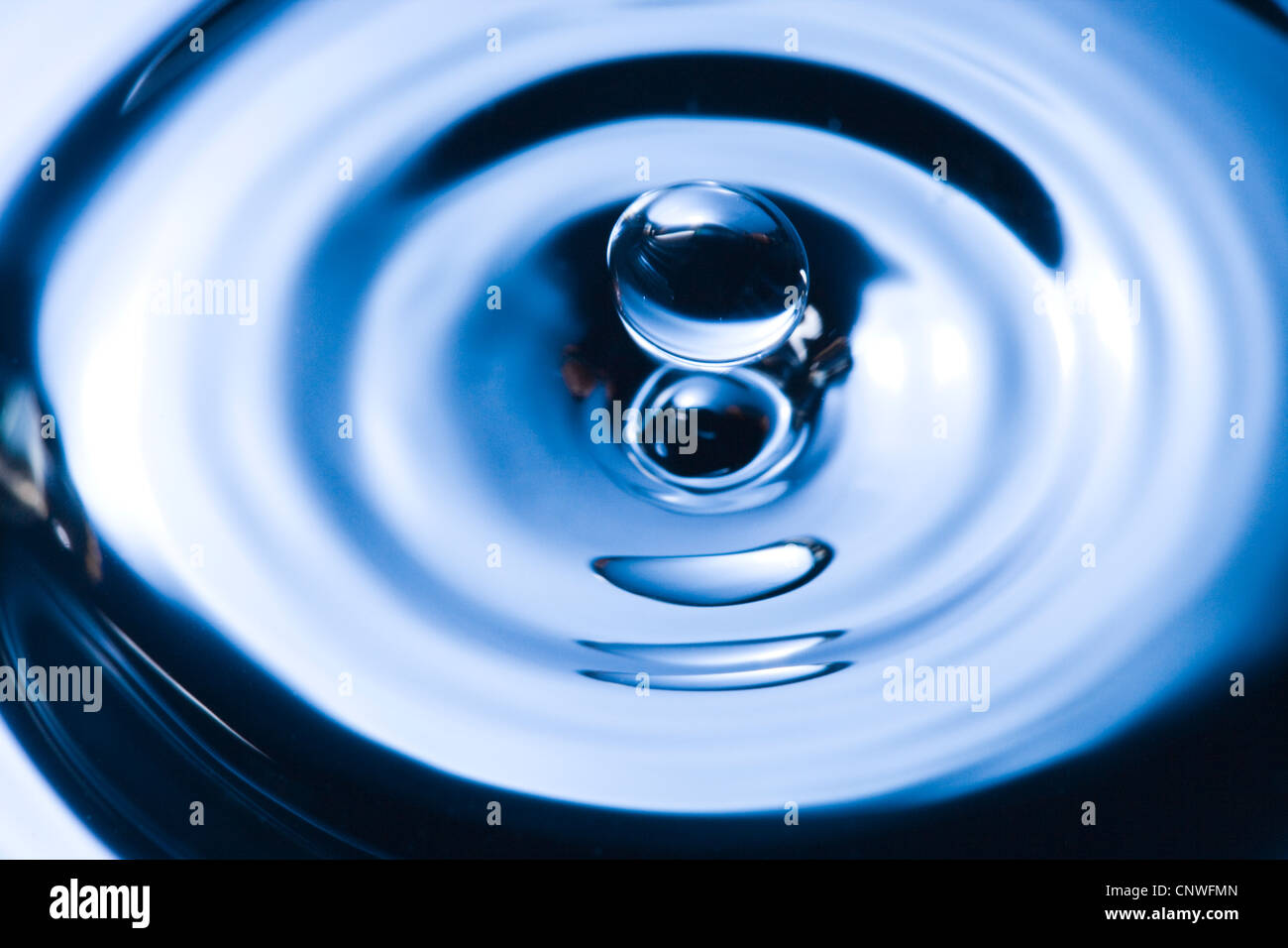 Water droplet causing ripples. - Stock Image