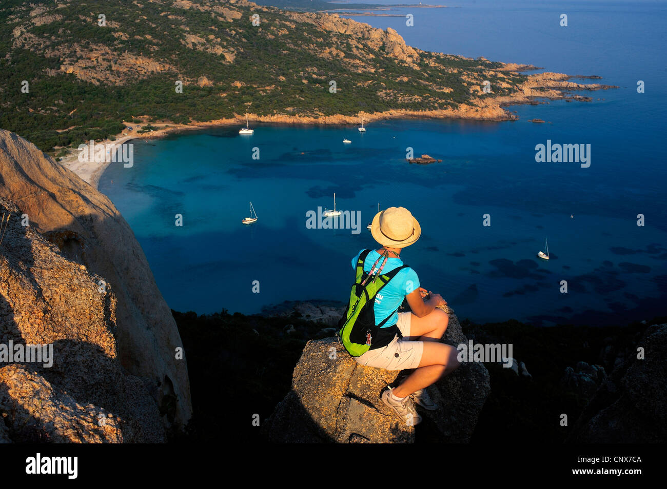 female hiker sittin on a rock over the bay of Roccapina, France, Corsica - Stock Image