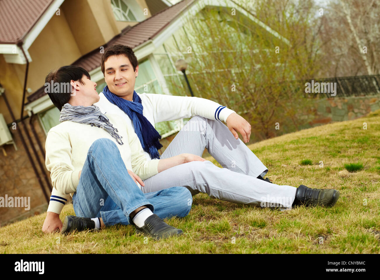 Tilt-up shot of young people looking at each other lovingly sitting on a grassy slope - Stock Image
