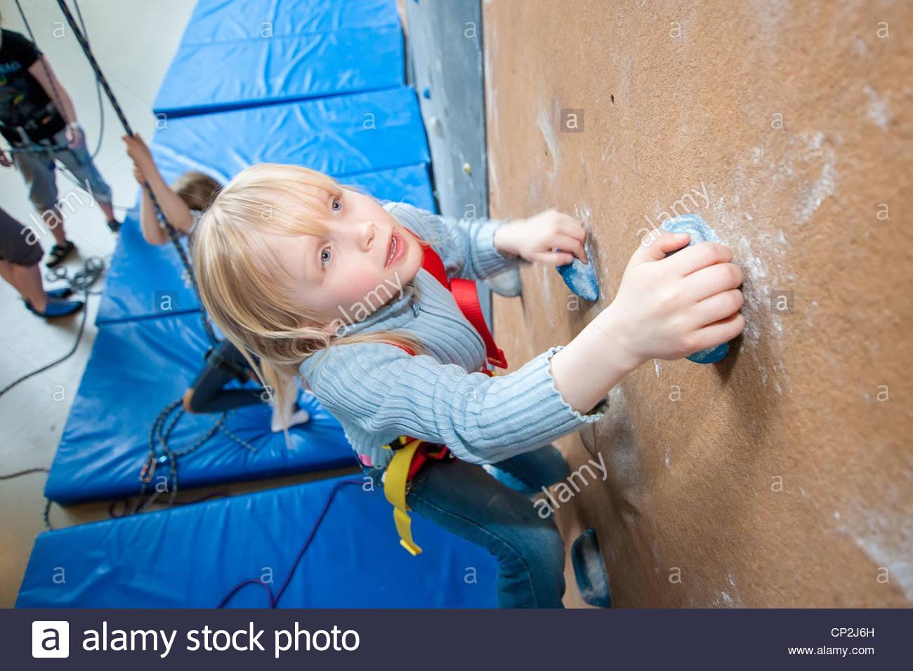 A little girl climbing in an indoor climbing wall - Stock Image