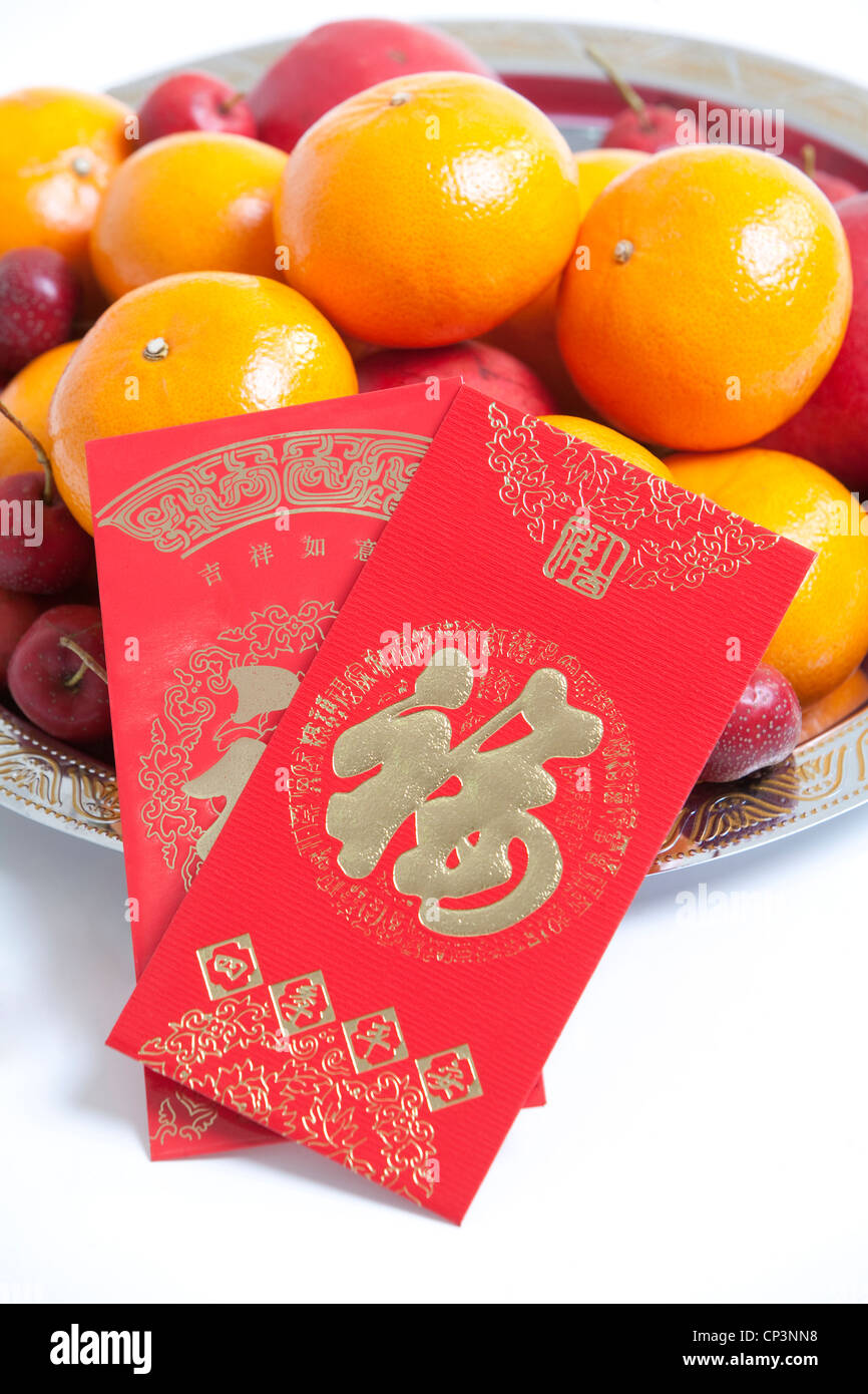 Red envelopes on bowl of fruit to celebrate Chinese New Year - Stock Image