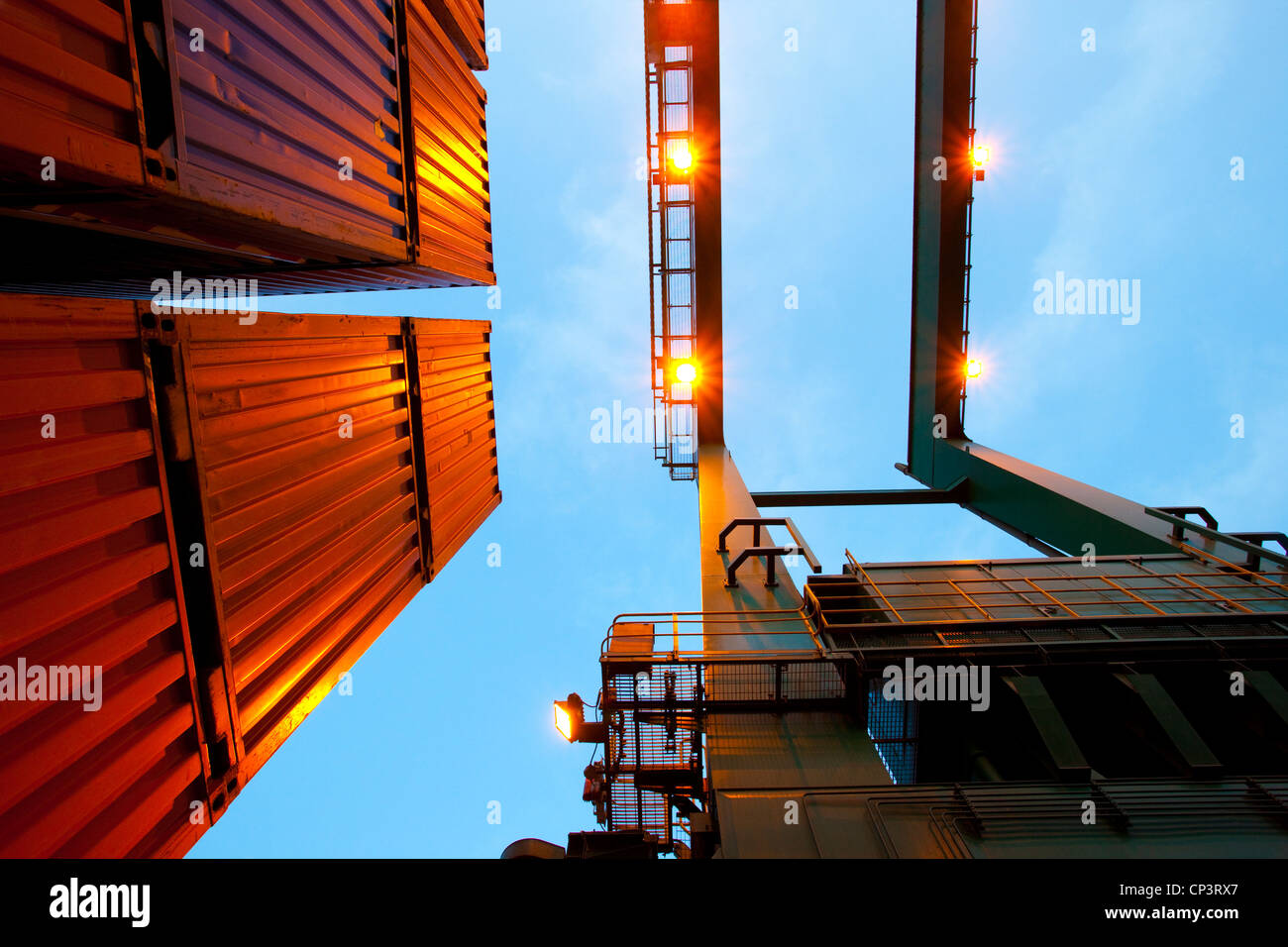Bottom view of cranes and stack of cargo containers - Stock Image