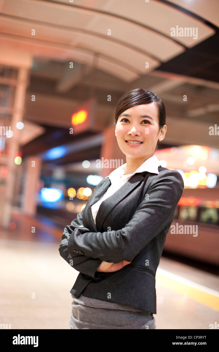 Young businesswoman contemplating at the train station - Stock Image