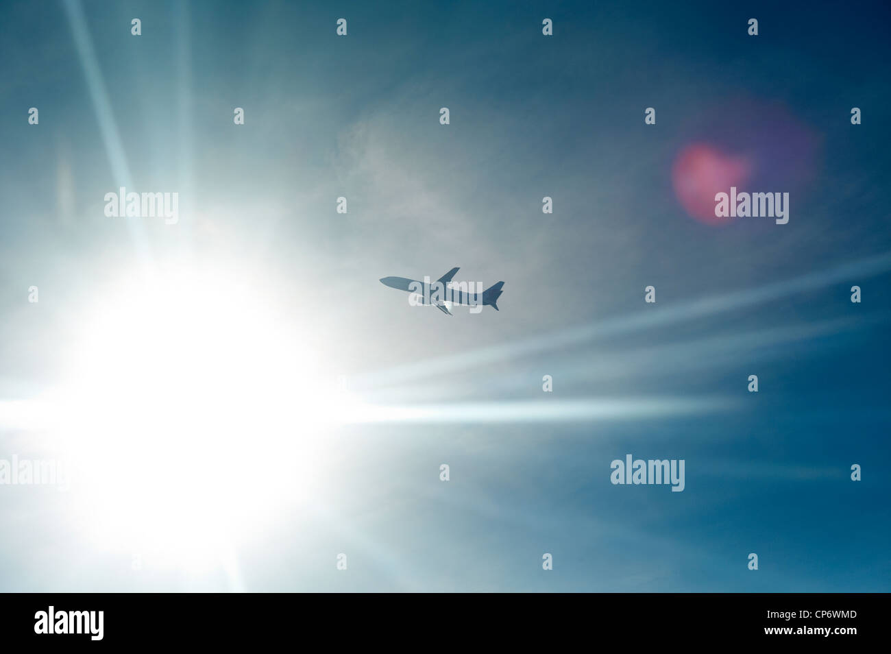 An airplane backlit by the sun in midair - Stock Image