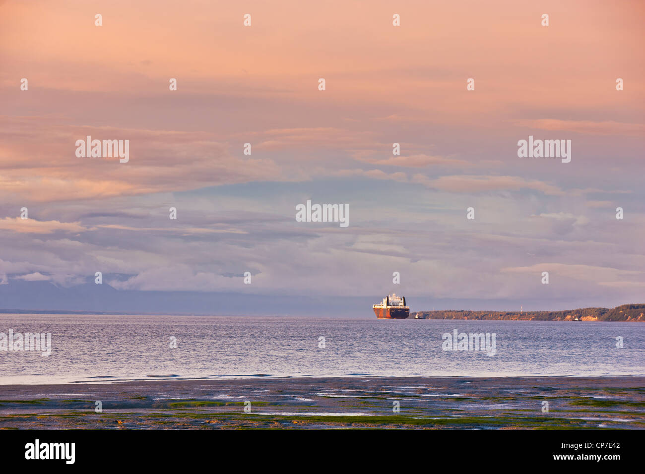 Sunset light illuminates a cargo ship comming in to dock at the Port of Anchorage, Knik Arm, Southcentral Alaska, - Stock Image