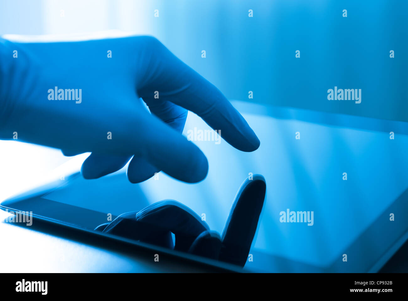 Hand in blue glove touching modern digital tablet. Concept image on medical or research theme. - Stock Image