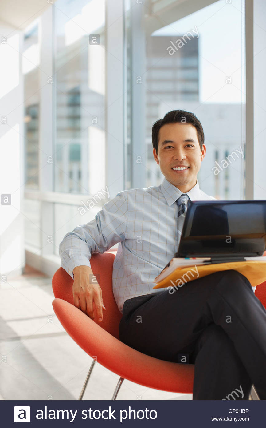30-34 years,accessibility,asian ethnicity,black hair,business,business attire,businessman,california,chair,color - Stock Image