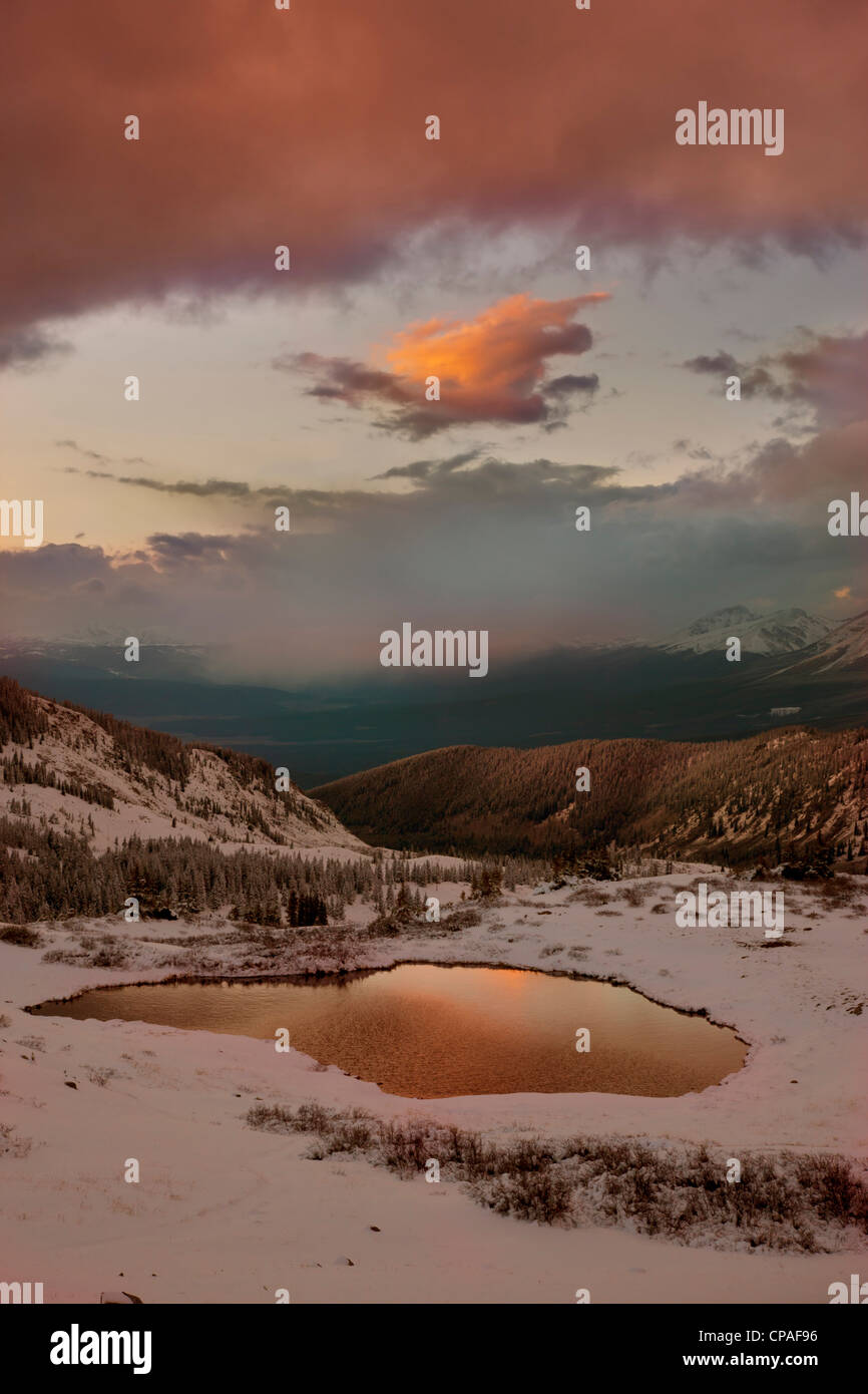 USA, Colorado, Cottonwood Pass. Sunset on alpine tarn ringed with fresh snow - Stock Image