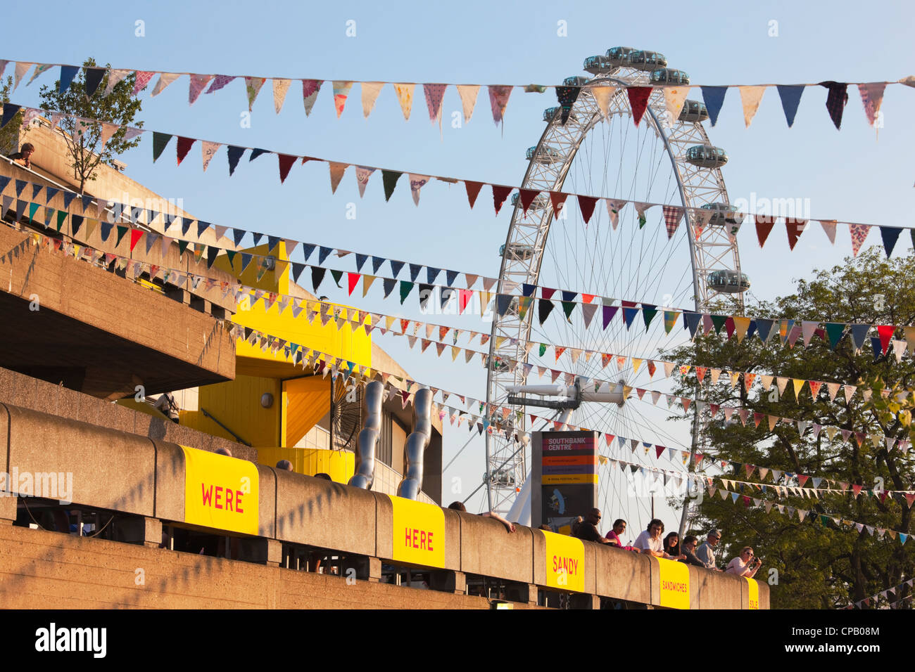 People leaning over balcony of BFI in front of London Eye; London; England - Stock Image