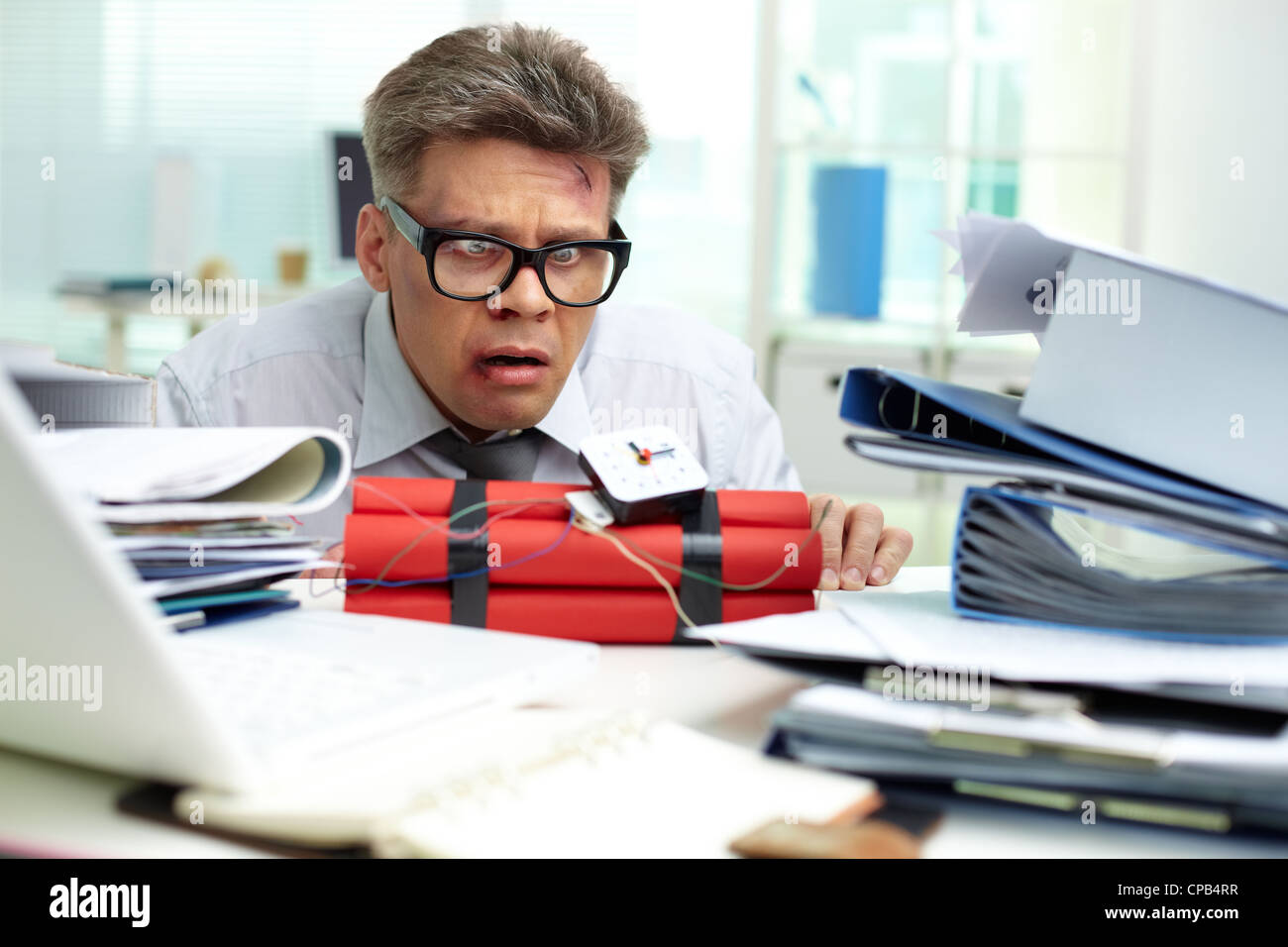 Terrified businessman looking at dynamite - Stock Image