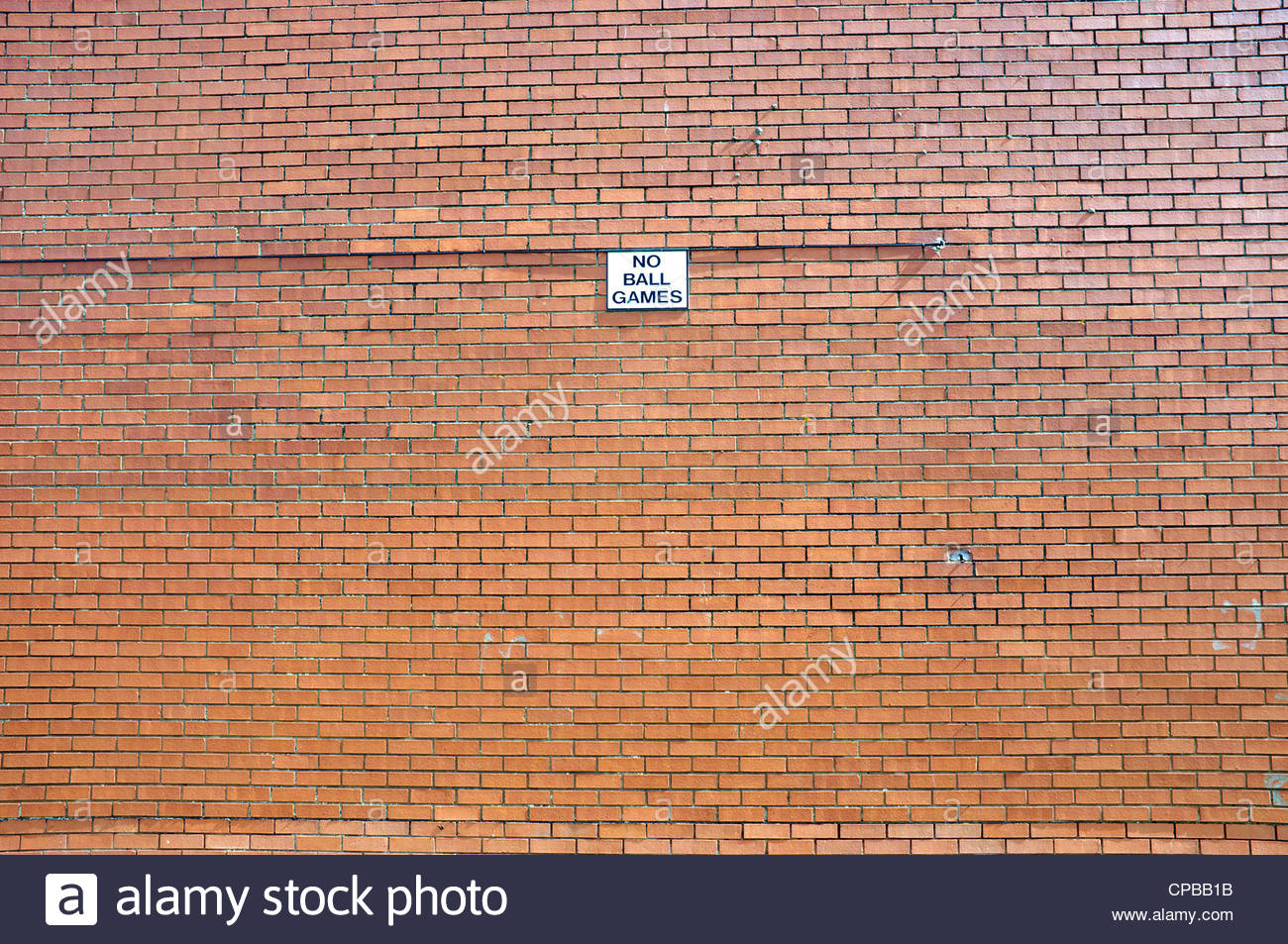 Sign 'No Ball Games' on a red brick wall, UK. Stock Photo