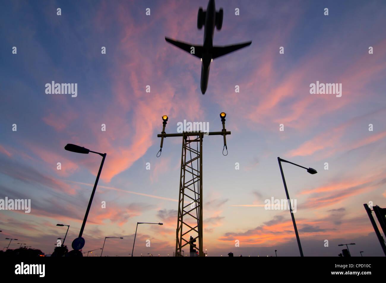 DC9 aircraft approaching over runway landing light gantries at sunset, London, England, United Kingdom, Europe - Stock Image