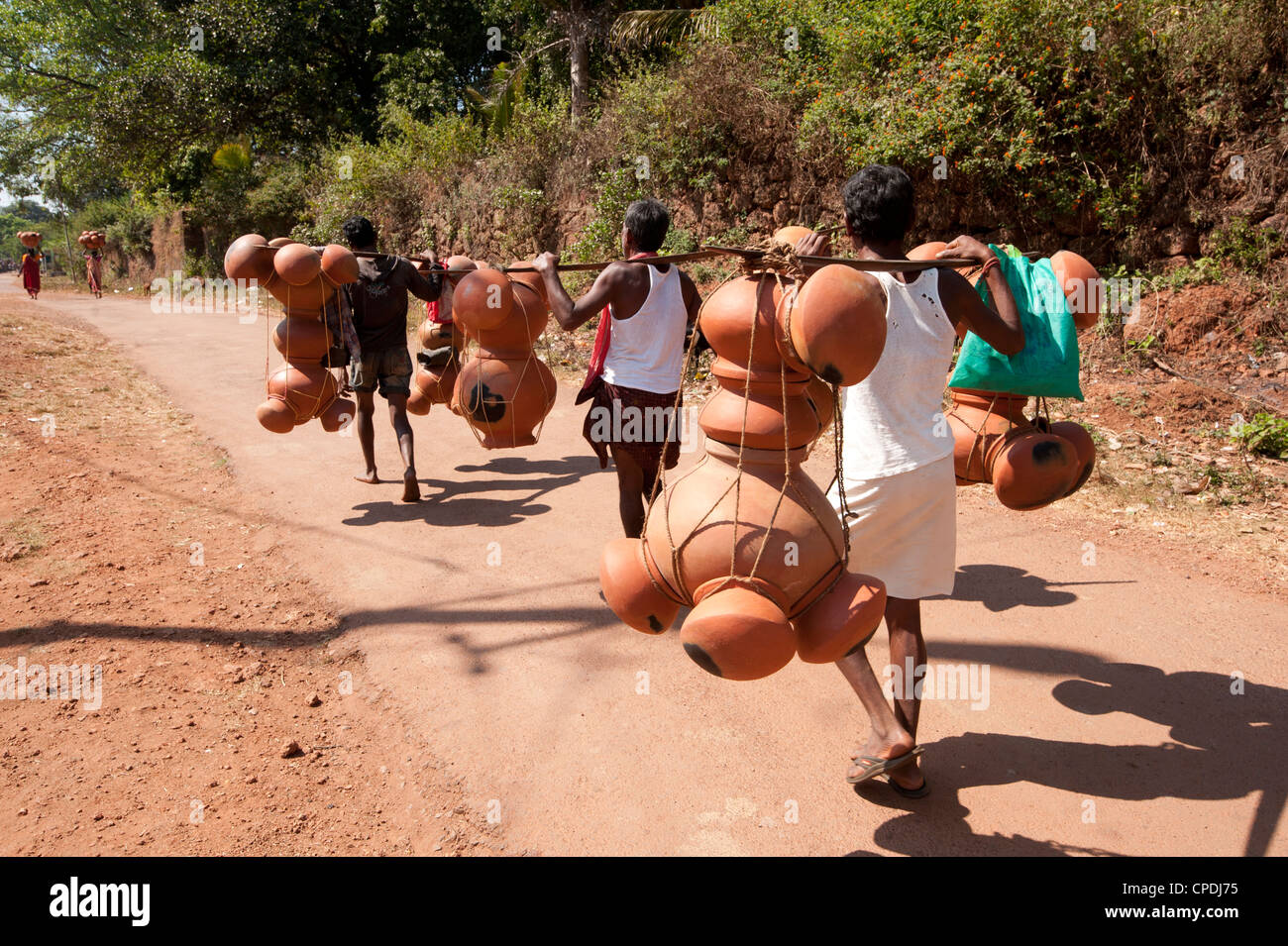 Bonda tribesmen walking to market carrying pots intended for village alcohol production, rural Orissa, India, Asia - Stock Image