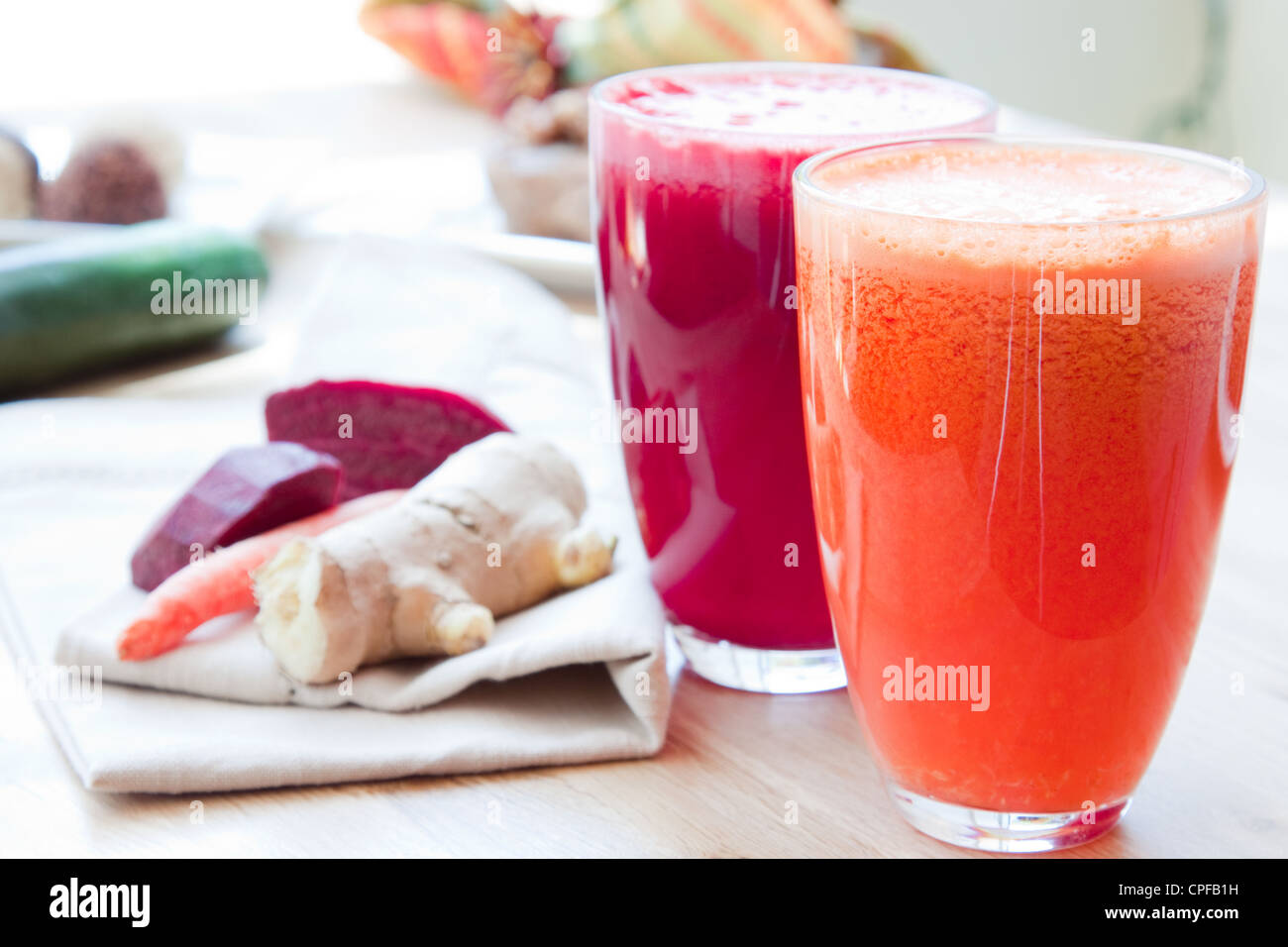 Two glasses of healthy juice - Beet, Apple, Carrot, Ginger and Orange, Apple, Pineapple. Ingredients in the background. - Stock Image