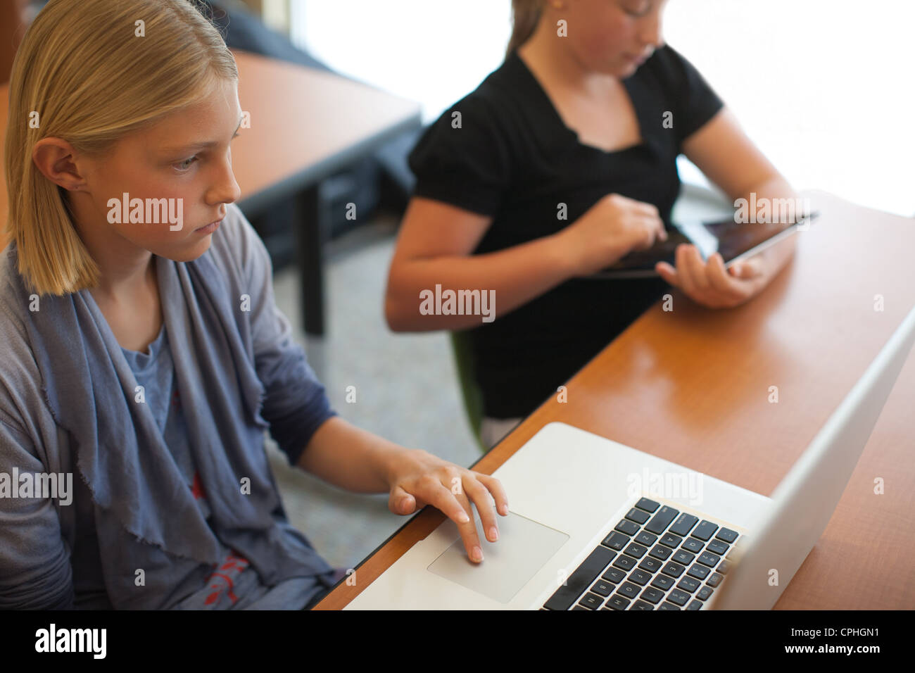Two middle school girls using technology in a classroom; laptop computer and ipad. - Stock Image