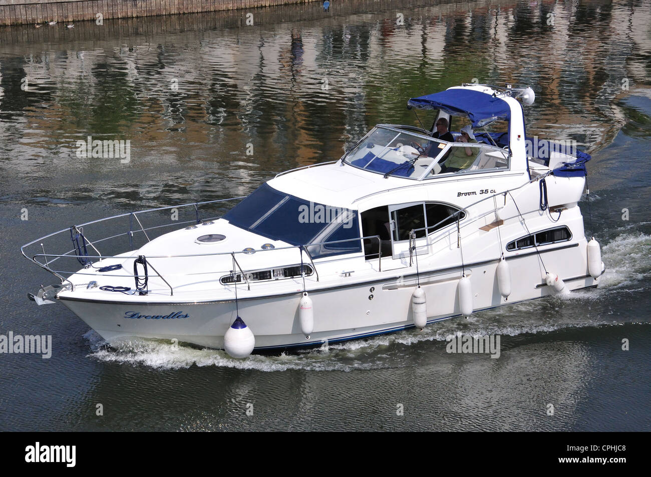 Motor boat cruising down River Thames, Thames Edge, Staines-upon-Thames,  Surrey, England, United Kingdom