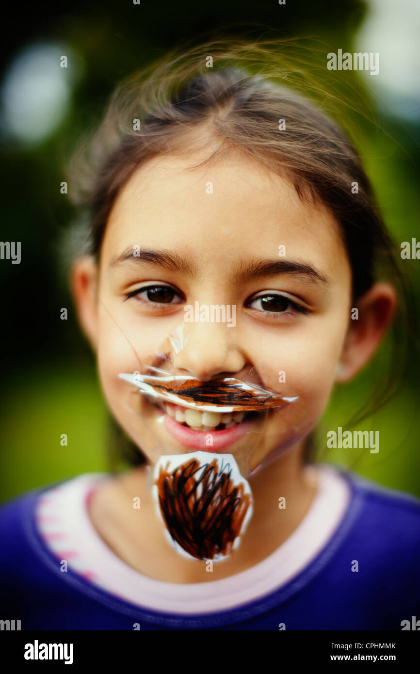 Movember. Girl with her homemade moustache and beard which she has stuck to her face with sticky tape. - Stock Image
