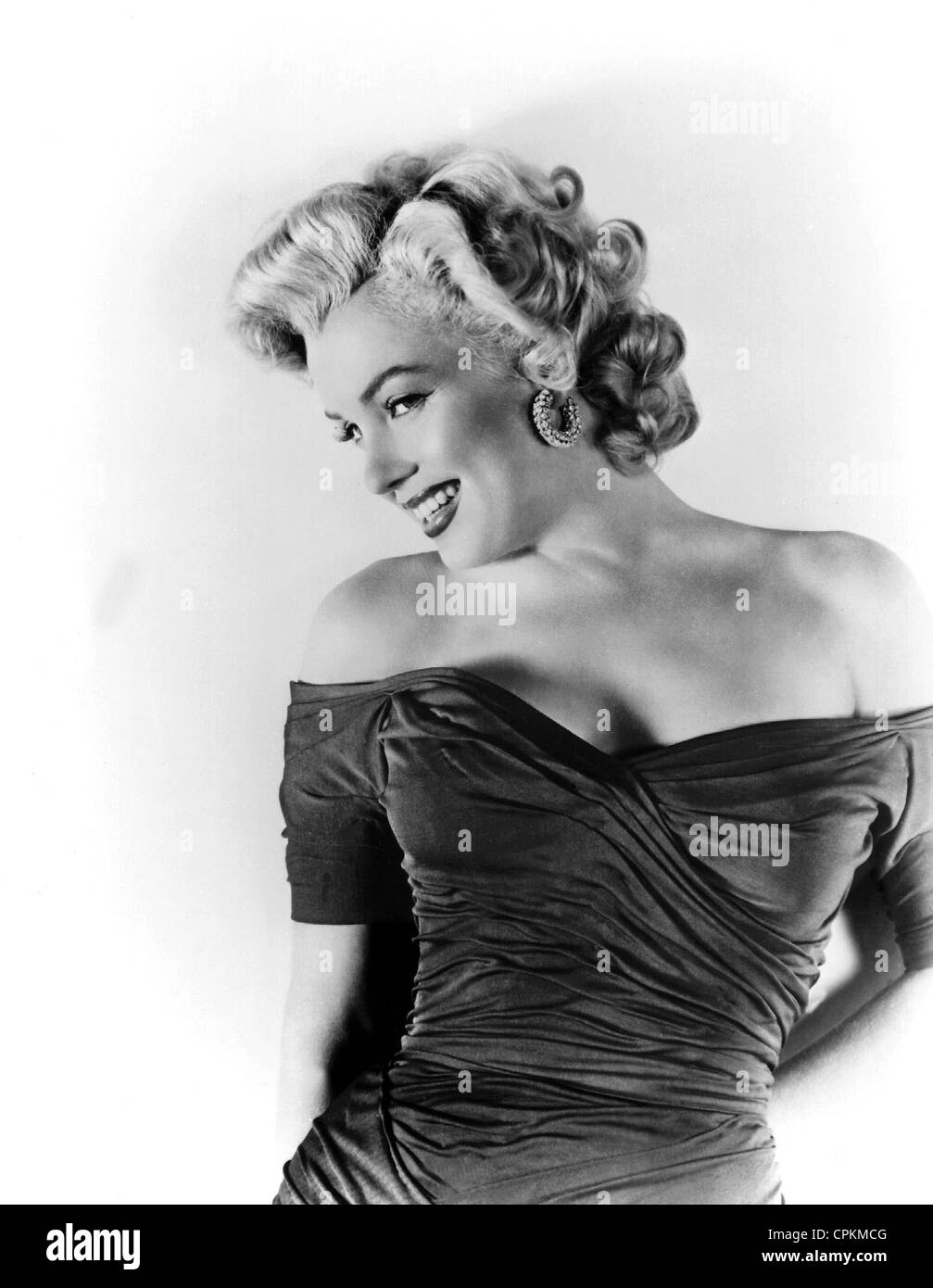 A color portrait of the film star Marilyn Monroe, pictured in 1957. She is smiling at the camera in this half body - Stock Image