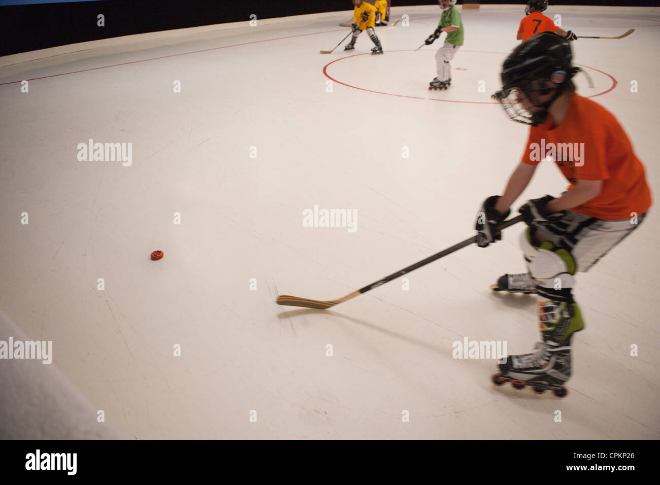 Hockey player skating in rink, youth hockey league, aiming for puck. - Stock Image