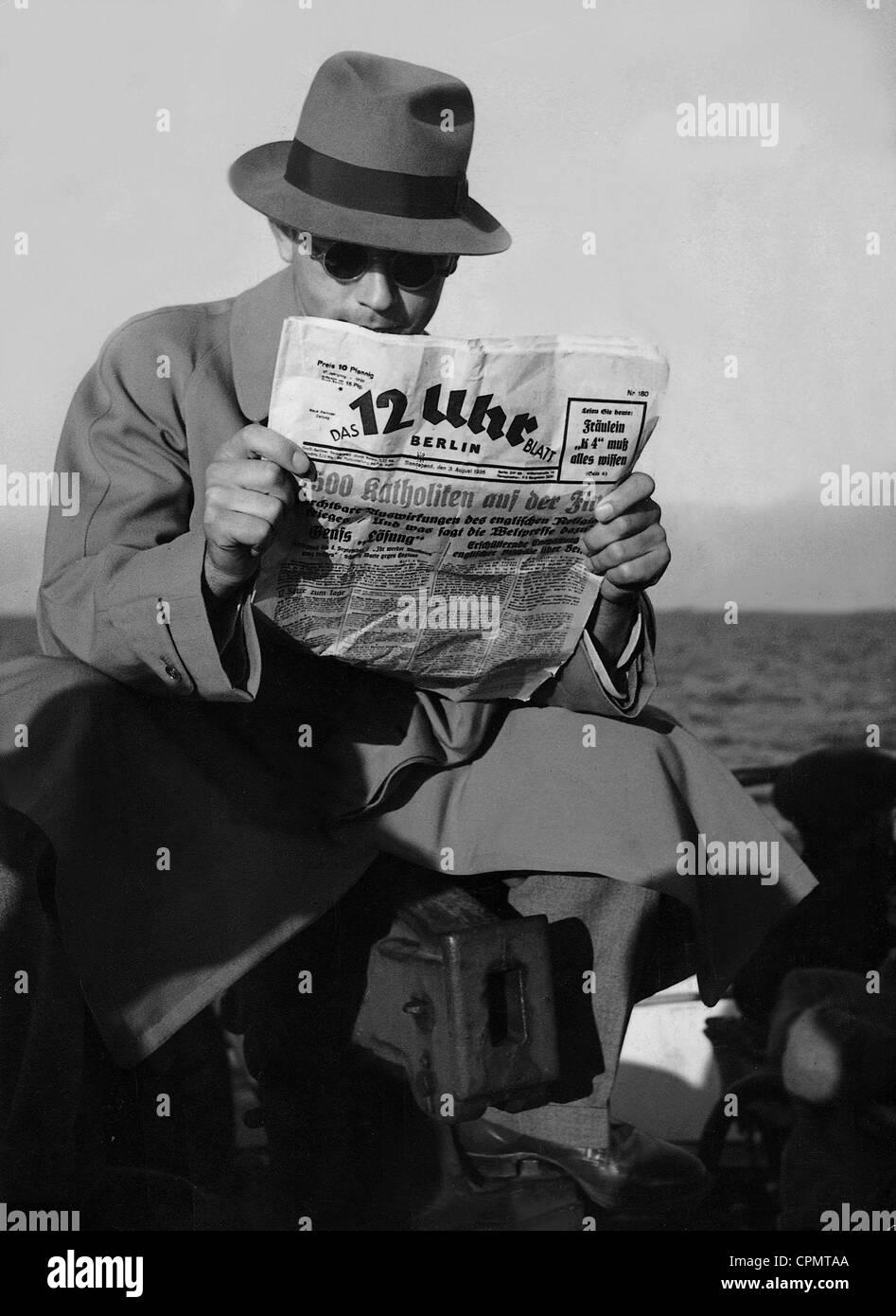 Man reading the newspaper '12 Uhr Blatt' - Stock Image