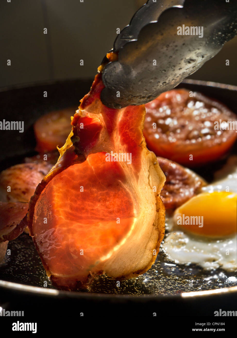 Shaft of sunlight illuminates a rasher of organic back bacon being turned in a hot frying pan containing fried egg - Stock Image